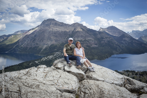 Fototapeta horizontal image of a caucasian husband and wife sitting together on top of a mountain with the lake and mountains in the background obraz na płótnie