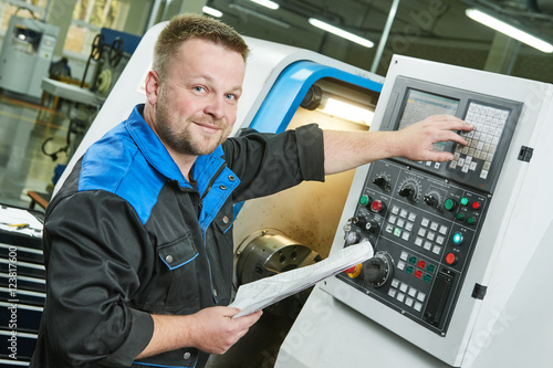 Fotografía  industrial worker operating cnc turning machine in metal machining industry