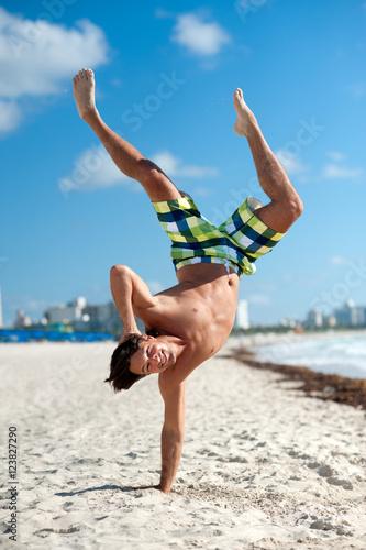 Plakat Młody człowiek robi Handstand na plaży