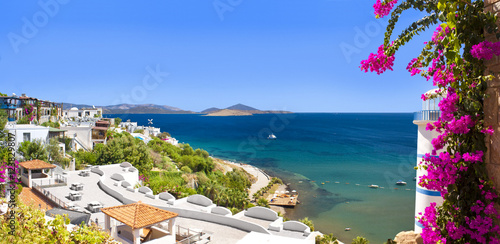 Stampa su Tela  Beautiful flowers frame a sea view of Ortakent, Bodrum, Turkey