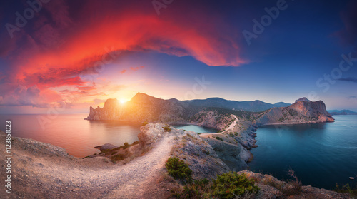 Spoed Foto op Canvas Cappuccino Amazing summer landscape with mountains, sea, blue sky, sun and beautiful colorful red clouds at sunset in Crimea. Sunset in mountains. Panoramic. Nature background. Vibrant landscape in twilight.