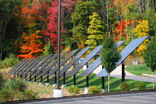 Solar Panels In A Row In Front Of Colorful Autumn Forest