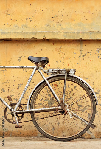 Staande foto Fiets Rusty Chinese bike against weathered yellow wall