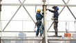 Industrial Climber Works at a Height of Weld Design.