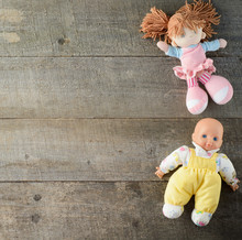 Dolls On Wooden Background. Top View. Copy Space.