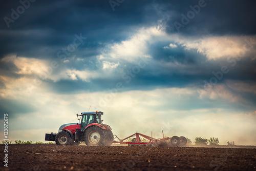 Farmer in tractor preparing land with seedbed cultivator Obraz na płótnie