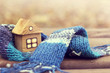 canvas print picture -  property insurance/ small wooden house in a warm blue scarf