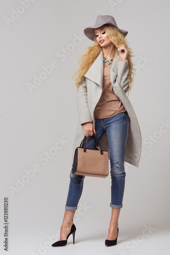 Spoed Foto op Canvas Boerderij Fashion blonde model in nice clothes posing in the studio. Wearing coat, hat, handbag, ripped jeans