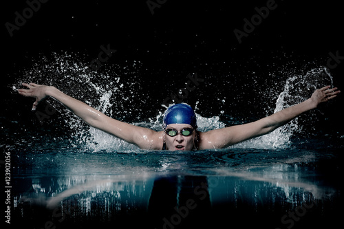 Profesional woman swimmer swim using breaststroke technique on the dark backgrou Fototapeta