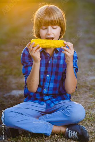 Fototapeta Happy boy eating healthy corn on the cob obraz na płótnie