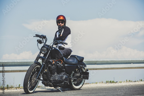 Biker standing by cruiser motorcycle on roadside against sky Poster