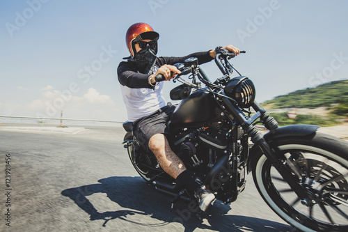 Man riding cruiser motorcycle on road against sky Poster
