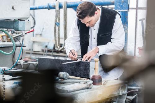Fotografía  Handwerker zeichnet Gravuren für Grabmale vor