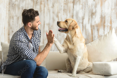 happy guy sitting on a sofa and looking at dog