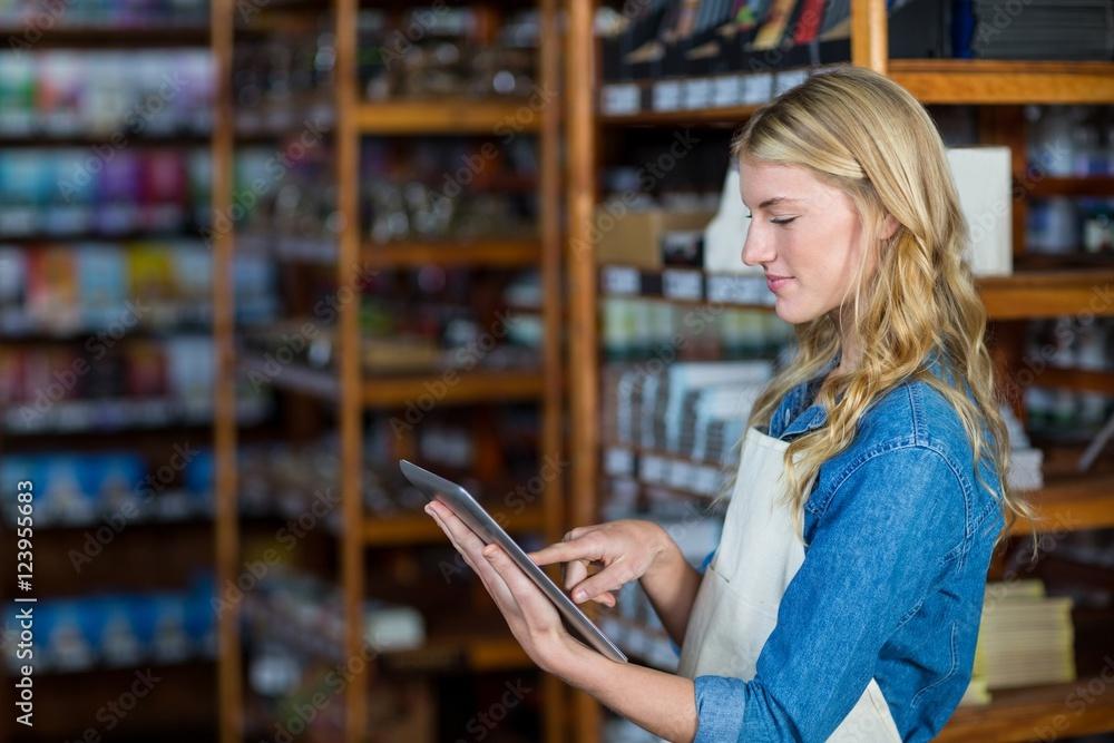 Fototapeta Female staff using digital tablet in supermarket