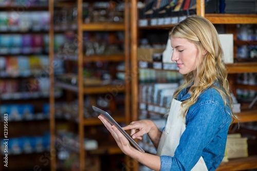 Female staff using digital tablet in supermarket Wallpaper Mural