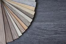 Laminate Wood Concept - Samples Of Laminate And Vinyl Floor Tile On Black Wooden Background.