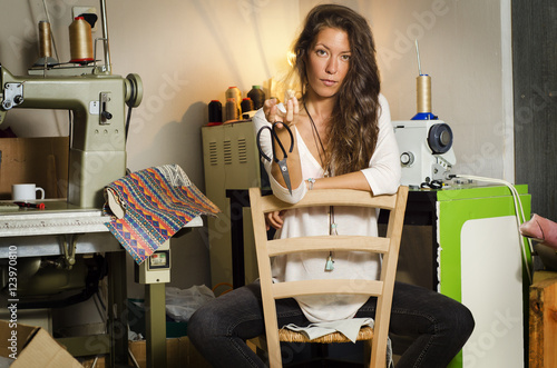 Fotografie, Obraz  Beautiful fashion designer girl, posing in her workshop, holding scissors
