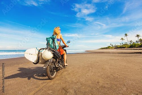 wonderful trip - woman riding a motorcycle with the surfboard