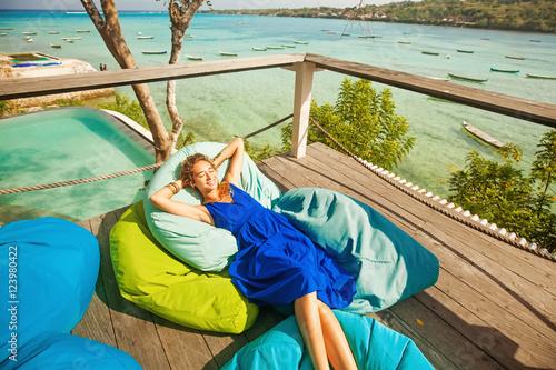 Photo woman on a bright beanbag chair on a balcony