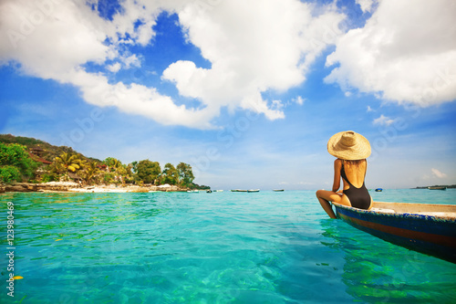 Cadres-photo bureau Bali back view of a woman sailing a boat in a paradise island