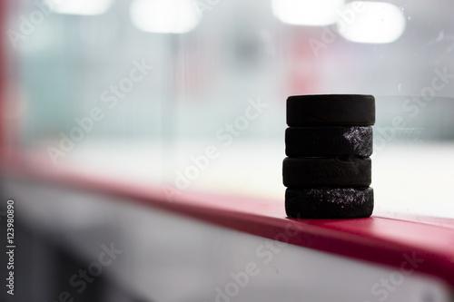 Photo  Hockey pucks along the boards
