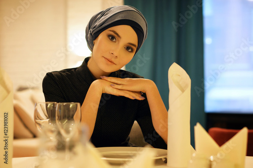Photo  portrait of a beautiful Muslim woman sitting at a table in a restaurant and look