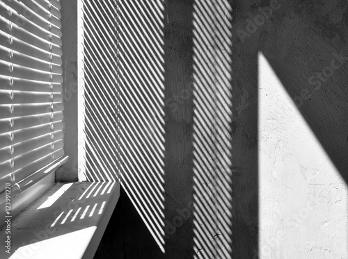 obraz lub plakat Geometric black and white composition. The plane of the plaster wall with a structural graphic shadow falling from the blinds. Horizontal view.