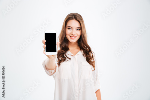 Fotografía  Smiling woman showing blank smartphone screen isolated on white background