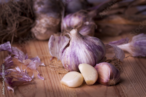 Fototapeta Garlic on wooden background - whole, sliced obraz