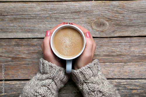 Fotografie, Obraz  Woman hands holding cup of coffee on wooden table