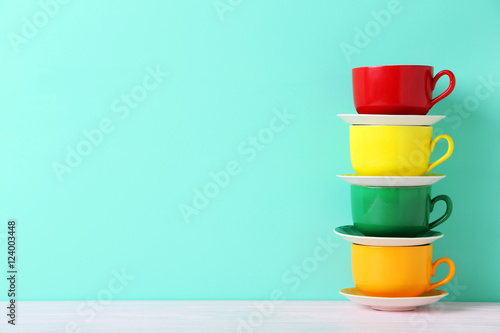 Colorful cups on a white wooden table