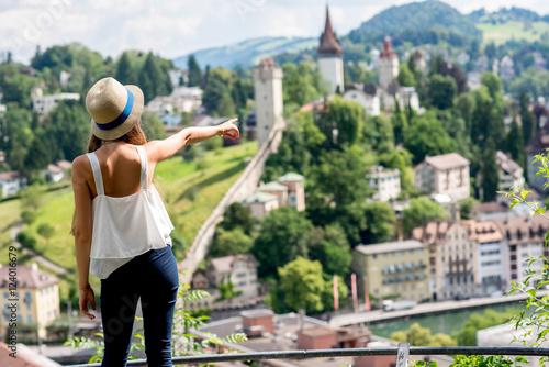 Valokuva Young female traveler enjoying great view on Lucerne cityscape in Switzerland