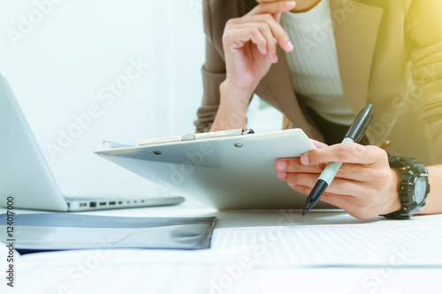 Valokuva  Business documents on office table with laptop computer,document business diagram and officer working in background,businesswoman meeting business plan
