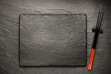 Two Chopsticks On Black Stone Background With Copyspace, Top View