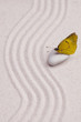 An yellow butterfly in a zen garden with white sand