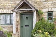 English Old Stone Cottage With Green Doors, Wooden Entrance Canopy And Herbs, Colorful Flowers Planted In Front Garden