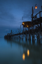 Lights On A Wooden Pier Leading Out In The Water At Night; Kho Samet,Thailand