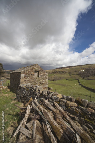 Tuinposter Hout A Pile Of Wood Laying Beside A Stone Wall And A Stone Building; Swaledale, England