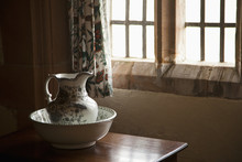 A Pitcher And Basin Sit On The Table Beside A Window; Lindisfarne, Northumberland, England