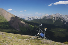 A Weather Station On Top Of A Ridge With Mountains And Valley In The Distance And Blue Sky With Clouds; Alberta, Canada