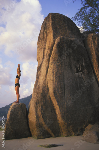 A Woman Tourist Stretches And Does Yoga On A Beach Of A Tropical Island; Koh Tao, Thailand