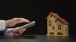 Businessman holds a tablet PC at the hands near a house model on a table (close up)