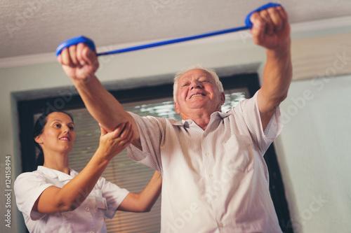 Fototapeta Senior man doing exercises using a strap to extend and strenthen obraz na płótnie