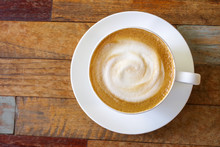 Top View Of Hot Coffee Cappuccino Cup With Milk Foam On Plank Wood Table Background.