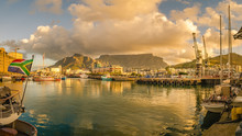 Cape Town Victoria And Alfred Waterfront Harbor At Sunset, Boat With South Africa Flag. Table Mountain, South Africa Beautiful Landscape