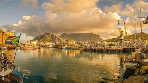 Fototapeta premium Cape Town Victoria and Alfred Waterfront port o zachodzie słońca, łódź z flagą Republiki Południowej Afryki. Table Mountain, Republika Południowej Afryki piękny krajobraz