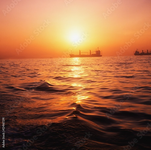Freighters On The Ocean At Sunset; Ireland