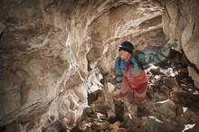 Female Athlete Exploring A Cave; Fernie, British Columbia, Canada