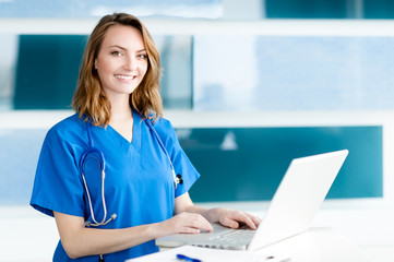 Attractive young woman doctor nurse practitioner in hospital clinic medical office with laptop